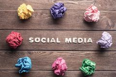 Social media phrase and colorful crampled paper ball placed in circle on wooden table. Set of multiple colorful crampled paper ball placed in circle on wooden royalty free stock images