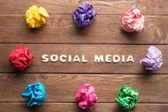 Social media phrase and colorful crampled paper ball placed in circle on wooden table. Set of multiple colorful crampled paper ball placed in circle on wooden royalty free stock photo