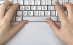 Social Media spelled out on a computer keyboard. A computer keyboard with typing hands and social media spelled out on the keys Royalty Free Stock Image