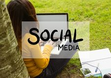 Social media text and white box against woman with laptop under tree Stock Image