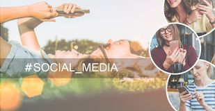 Social media.Two young women lie on the lawn, listen to music and use a smartphone. Stock Photo