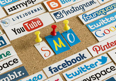 Social media website logos Facebook, Twitter and letters SMO printed on paper and pinned on cork bulletin Stock Images