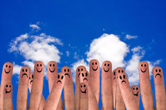 Social network. Group of finger faces on the sky background Royalty Free Stock Image