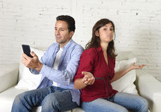 Social network addict man using mobile phone ignoring wife or girlfriend upset and angry Royalty Free Stock Photography