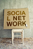 Social network. On cardboard left on empty chair in obsolete room Stock Photography