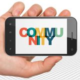 Social network concept: Hand Holding Smartphone with Community on  display. Social network concept: Hand Holding Smartphone with Painted multicolor text Royalty Free Stock Images