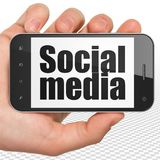 Social network concept: Hand Holding Smartphone with Social Media on display Stock Images