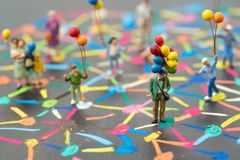 Social network concept, miniature people holding balloons standing on colorful pastel chalk line link and connect between. Multiple dot or teer on blackboard stock photography
