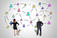 Social network concept watched by business people. Social network concept drawn on a wall watched by business people stock image
