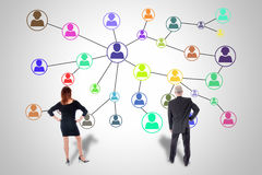 Social network concept watched by business people. Social network concept drawn on a wall watched by business people royalty free stock photos
