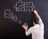 Social network. Man is looking for a new ideas for business. Blackboard with connecting jigsaw pieces Stock Photo