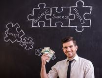 Social network. Smiling man is holding money and looking for a new ideas for business. Blackboard with connecting jigsaw pieces Stock Photography