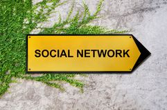 Social network on yellow sign hanging on ivy wall. Concrete texture Royalty Free Stock Photo