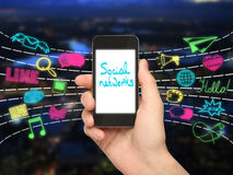 Social networking concept. Hand holding cellular phone with text on screen and colorful media icons on city background. Social networks concept Royalty Free Stock Photo