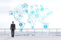 Social networking. Concept with thoughtful businessman looking at abstract network with people icons on city background Royalty Free Stock Photo
