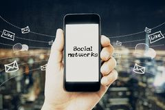 Social networking and media concept. Hand holding smartphone with creative network sketch on blurry night city background. Social networking and media concept royalty free stock images