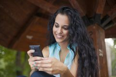 Networking - mixed race young smiling woman use mobile phone to Royalty Free Stock Photo