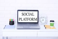 Social platform. Words on screen. Workplace with computer, cup of coffee and notebook. Stylish copy space. Mock up Stock Image