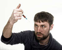 The social problem - addiction. Young sad man holding syringe to drug use Royalty Free Stock Image