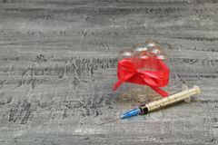 Social problem. Drugs and society. Used syringe with steel needle and empty glass ampoules which are tied up by red thin tape on stock photo