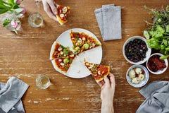 Social que recolhe comer e compartilhar da pizza orgânica Imagem de Stock Royalty Free