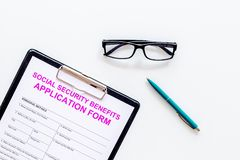 Social security benefits. Application form near pen and glasses on white background top view space for text royalty free stock images