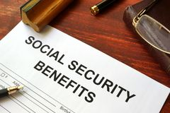 Social security benefits form and glasses. Social security benefits form, book and glasses royalty free stock image