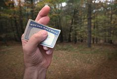 Social security card in crossed fingers stock photography