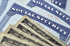 Social Security Cards and Cash Money. Detail of several Social Security Cards and cash money symbolizing retirement pensions financial safety stock photo