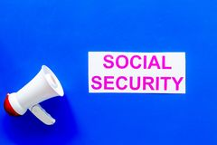 Social security concept. Printed words social security near megaphone on blue background top view copy space royalty free stock images