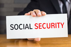 Social security, message on white card and hold by.  Stock Image
