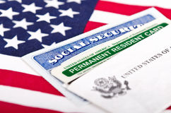 Social security and permanent resident card. United States of America social security and green card with US flag on the background. Immigration concept. Closeup