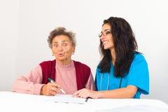 Social Service Provider Helping Elderly. Social service provider nurse helping elderly in homecare with bills royalty free stock photo
