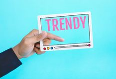 Social trendy and online marketing concepts with male hand holding fram of video movie and text on blue color background. Digital trending ideas stock photography