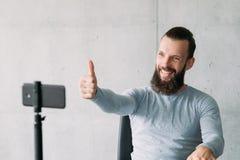 Social vlog man smartphone encourage subscribers. Social vlog. Bearded man using smartphone on tripod to encourage subscribers with thumb up gesture. Copy space royalty free stock photos