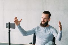 Social vlog man smartphone share experience. Social vlog. Bearded man using smartphone on tripod to share experience with public. Copy space stock photo