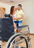Social worker assisting girl during rehabilitational  period. Young social worker assisting girl during rehabilitational  period at home. Focus on wheelchair Stock Images