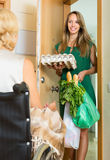 Social worker bringing food to invalid. Smiling young female social worker bringing food to invalid's home royalty free stock photo