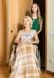 Social worker and disabled woman. Positive social worker and disabled female on chair returning home Stock Photo