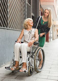 Social worker and disabled woman at stroll Royalty Free Stock Photos