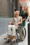 Social worker and disabled woman at stroll Stock Images