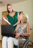 Social worker and handicapped woman with laptop Royalty Free Stock Images