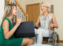 Social worker and handicapped woman with laptop Stock Photography