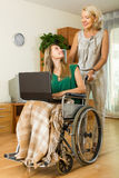 Social worker and invalid with laptop Royalty Free Stock Photo