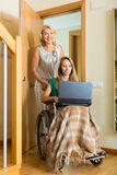 Social worker and invalid with laptop Stock Photos