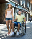 Social worker taking invalid for a walk. Female social worker taking young men in invalid chair for a walk. Focus on man Royalty Free Stock Images