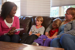 Social Worker Talking To Mother And Children At Home. Whilst Sitting On Sofa Smiling At Each Other stock photo