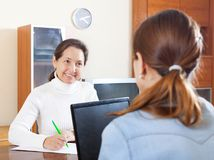Social worker women. Mature women answer questions of outreach worker with laptop at table in home Royalty Free Stock Photo