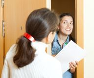 Social worker women. Woman answer questions of outreach worker with papers at door in home Royalty Free Stock Images