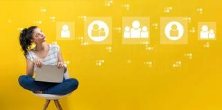 Sociala anslutningar med kvinnan som använder en bärbar dator arkivfoton